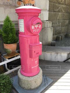 レンガの壁の隣に座っている赤い消火栓の写真・画像素材[2527042]