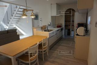 木製キャビネット付きのキッチン、ダイニングルームテーブルの写真・画像素材[2543703]
