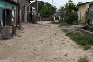 建物の前の泥道を歩く人々のグループの写真・画像素材[2540717]