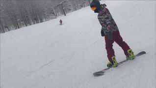 雪に覆われた斜面を雪に乗った若者の写真・画像素材[2531498]