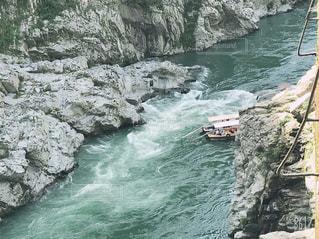 水の隣の岩の上の人々のグループの写真・画像素材[2541425]