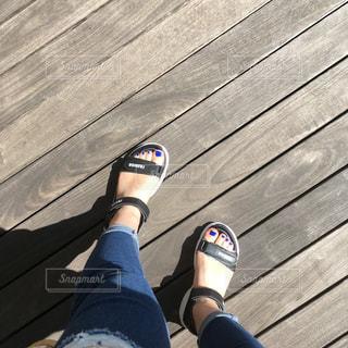 木製の板の上で黒の靴を履いた足のクローズアップの写真・画像素材[2530045]