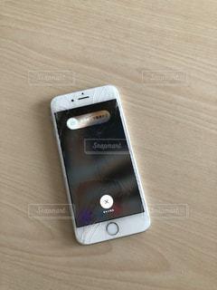 テーブルの上に座っている携帯電話の写真・画像素材[3333676]