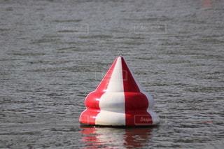 水の体の隣に座っている赤と白のボートの写真・画像素材[3277058]