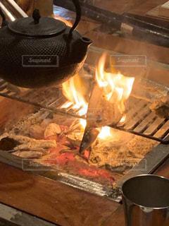 暖炉の隣に座るストーブトップオーブンの写真・画像素材[2550239]