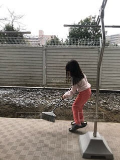 ベランダの掃き掃除する娘の写真・画像素材[4064945]