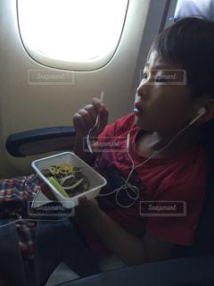 機内食を食べながら映画鑑賞する男の子の写真・画像素材[2553657]