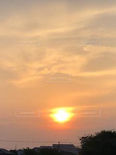 夕暮れの淡いオレンジの空と滲んだ夕日がある風景の写真・画像素材[2613215]