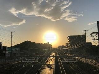 電線の連なる町並みの真ん中にある線路を走る列車と空に浮かぶ大きな夕日がある風景の写真・画像素材[2745910]
