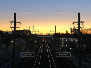 真っ直ぐ伸びた線路のレールと電柱がある街並みの夕暮れの風景の写真・画像素材[2936149]