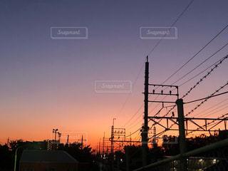 紫とピンクのグラデーションの夕焼けと線路の鉄線が連なる街並みの風景の写真・画像素材[2941330]