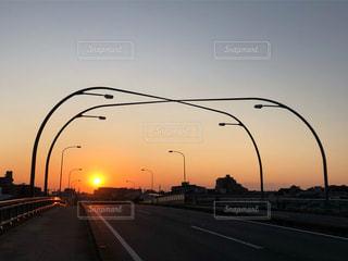 街路灯が連なる道路から見たオレンジの夕焼けと夕日のある風景の写真・画像素材[2941341]
