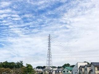 秋の雲が広がる空と高圧電塔が真ん中にある田舎の街並みの風景の写真・画像素材[3811181]