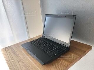 木製テーブルの上にある黒いノートパソコンがある部屋の風景の写真・画像素材[3813644]