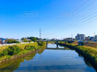 秋の青空に高圧電線が伸びる田舎の街並みと大きな川のある風景の写真・画像素材[3850570]