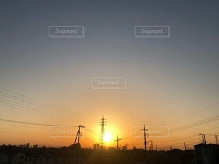 夕焼けのオレンジの空に浮かぶ夕日と高圧鉄塔と電線が連なる街並みの風景の写真・画像素材[3987155]