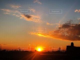オレンジ色の夕焼け空と夕日が沈む街並みの風景の写真・画像素材[4018323]