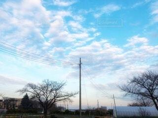 水色の空に浮かぶ白い雲と電線が連なる田舎の街並みの風景の写真・画像素材[4080447]