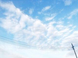 青空に広がる白い雲と電信柱から伸びる電線のある風景の写真・画像素材[4080446]