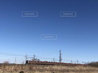 快晴の青空と架線が連なる線路を走る電車と田舎の長閑な風景の写真・画像素材[4173204]