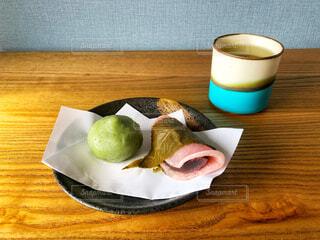 木製テーブルの上にあるお皿に盛られた桜餅と緑茶の入った湯呑みが置いてある部屋の風景の写真・画像素材[4250746]