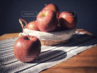 木製テーブルの上にあるバスケットに入った林檎のある風景の写真・画像素材[4442389]