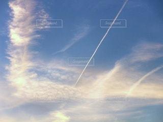 夕焼け雲に飛行機雲が流れるの写真・画像素材[2587603]