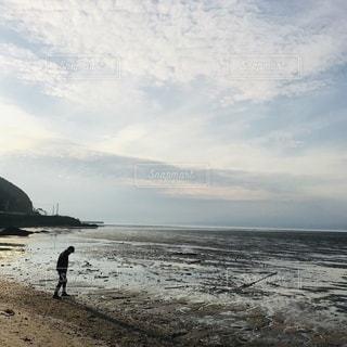 水の体の近くのビーチに立っている男の写真・画像素材[3338943]