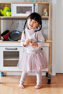 台所に立っている小さな女の子の写真・画像素材[2799258]