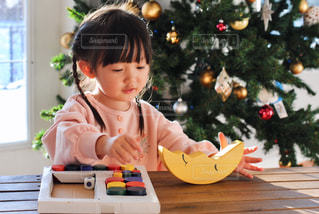 テーブルの上に座っている小さな女の子の写真・画像素材[2805987]
