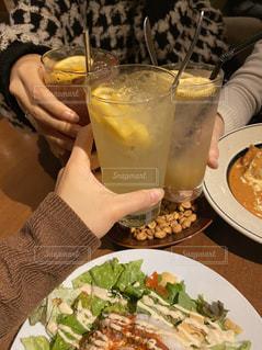 食べ物の皿を持ってテーブルに座っている人の写真・画像素材[2810304]