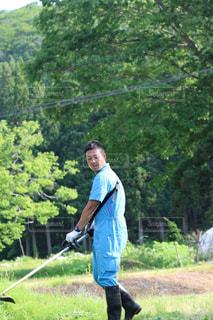 芝生に覆われた畑の上に立っている男の写真・画像素材[2818946]