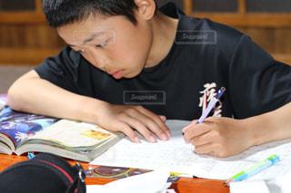 テーブルの上に座っている少年の写真・画像素材[2871738]
