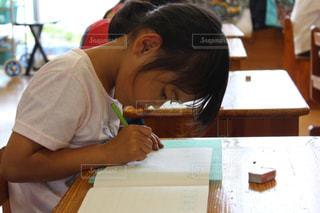 テーブルに座っている小さな女の子の写真・画像素材[2879399]
