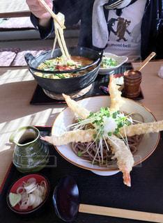 食べ物の皿を持ったテーブルに座っている人の写真・画像素材[3054040]