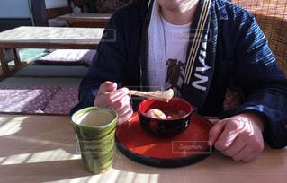 コーヒーを飲みながらテーブルに座っている人の写真・画像素材[3054069]