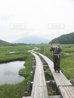 水の体に架かる橋の上に立っている男の写真・画像素材[3099908]