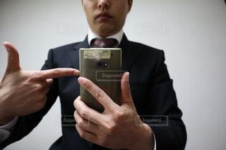 携帯電話を持ったスーツを着た男の写真・画像素材[3031743]