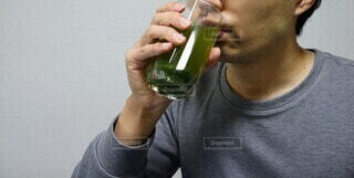 青汁を飲む男性のクローズアップの写真・画像素材[3936585]