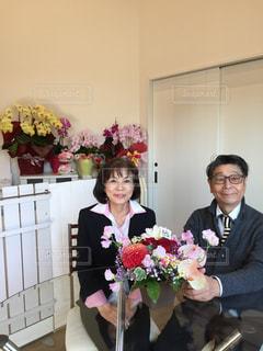 テーブルの上の花の花瓶の横に立っている人の写真・画像素材[994682]