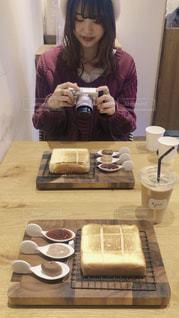 食べ物を持ってテーブルに座っている女性の写真・画像素材[3211177]