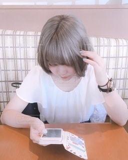 テーブルに座っている小さな女の子の写真・画像素材[3314224]