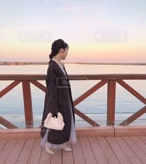水の体の隣の桟橋の前に立っている人の写真・画像素材[4034467]