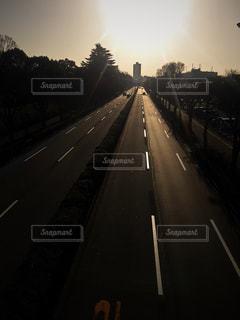 背景の夕日と長い道のりの写真・画像素材[1123989]