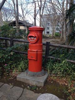 歩道の真ん中に座っている赤いポストの写真・画像素材[2683810]