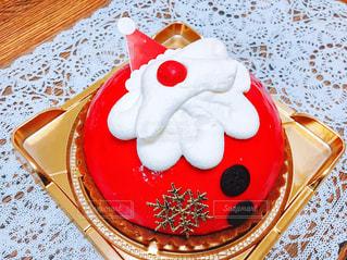テーブルの上に座っている赤と白のサンタケーキの写真・画像素材[2828008]