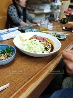 食べ物の皿を持ってテーブルに座っている人の写真・画像素材[2840665]