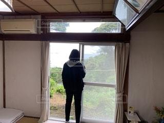 窓の前に立っている男の写真・画像素材[2684608]