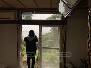 窓の前に立っている人の写真・画像素材[2684609]
