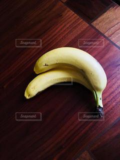 木製のテーブルの上に寝ているバナナの写真・画像素材[2902540]